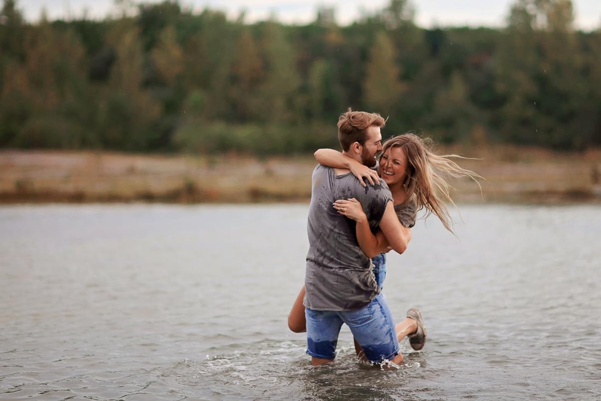 Man swinging women around in the water lovingly.